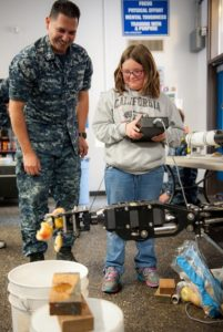 BREMERTON, Wash. (June 11, 2016) Sonar Technician (Submarines) 1st Class Ruben Villanueva watches as Hailey Hunt, 10, uses the controls of a manipulator on an Unmanned Undersea Vehicle to crush an apple during the 5th annual Remote Operated Vehicle (ROV) Competition at Olympic High School in Bremerton, Washington, June 11. Naval Undersea Warfare Center Keyport and Puget Sound Naval Shipyard and Intermediate Maintenance Facility personnel volunteered to help with the ROV programs for high school, junior high, and elementary students, which are designed to spark interest in science, technology, engineering and math (STEM). (U.S. Navy photo by Mass Communication Specialist 2nd Class Jacob G. Sisco/Released)