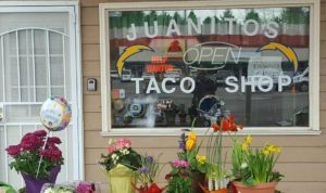 Flowers line the front of Juanitos Taco Shop on Kitsap Way, which was run by Christale and John Careaga. (Photo courtesy of GoFundMe page)